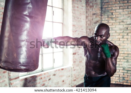 Black boxer punching the heavy bag in the gym
