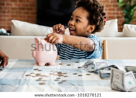 Black boy collecting money to piggy bank