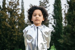 Black boy wearing a silver clothing, looking at the camera. In a park background. Copyspace. Kids, astronauts, extraterrestrials and black people concept