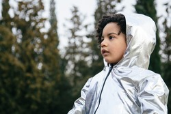 Black boy wearing a silver clothing, looking away. In a park background. Copyspace. Kids, astronauts, extraterrestrials and black people concept
