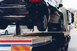 Black Broken Car on a Towing Truck. Closeup Photo. Vehicle Mechanical Problem or wrong parking on the Road.