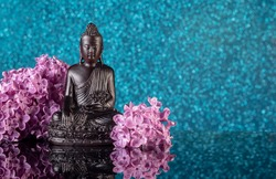 Black Buddha framed by lilac flowers on a blue bokeh background with reflection