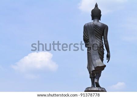 black buddha statue against blue sky in thai temple