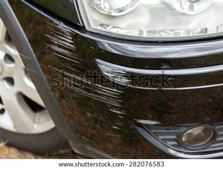 Black bumper car scratched with deep damage to the paint.