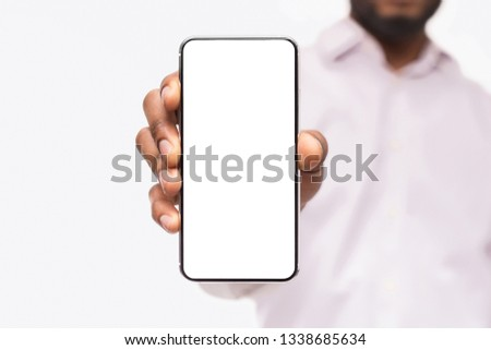 Black businessman showing smartphone with blank screen, isolated on white background, copy space #1338685634