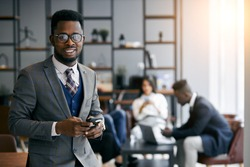 Black businessman wearing grey tuxedo holding smartphone during work time in modern office, business partners meeting background. Look at camera and smile. Business people concept