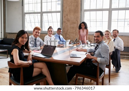 Black businesswoman and team at board meeting look to camera