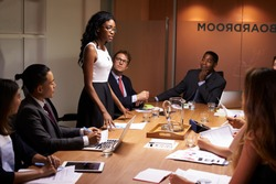 Black businesswoman stands addressing colleagues at meeting