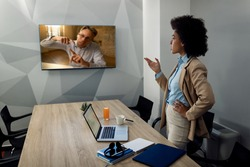 Black businesswoman talking to male colleague during a video call while working in her office.