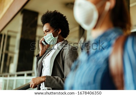 Black businesswoman wearing face mask as a protection against viruses and  talking on mobile phone while walking at airport terminal.