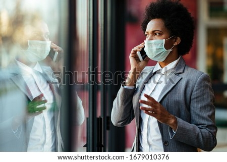 Black businesswoman wearing protective mask on her face and talking on smart phone while looking through the window.