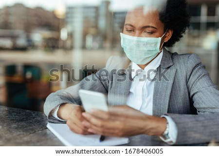 Black businesswoman wearing protective mask on her face while using smart phone and reading text message. The view is through the glass.