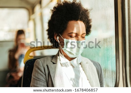 Black businesswoman with face mask listening music over earphones while commuting to work by bus during virus epidemic.