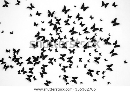 Black butterfly on a white background. Texture with butterflies. The decoration of the walls. Handmade. Black butterfly on a white field.