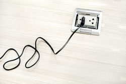 Black cable plugged in a white electric outlet mounted on floor