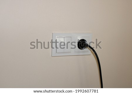 Black cable plugged into white electrical outlet Stok fotoğraf ©