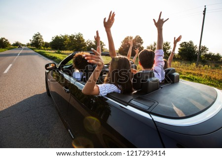 Black cabriolet is on the country road. Happy group of young girls and guys are sitting in the car hold their hands up on a sunny day.