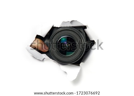 black camera with a telephoto lens that looks out through a hole in white paper. Concept of paparazzi, espionage, yellow press. camera lens looking through hole in wall.