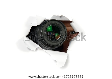 black camera with a telephoto lens that looks out through a hole in white paper. Concept of paparazzi, espionage, yellow press. camera lens looking through hole in wall. Foto stock ©