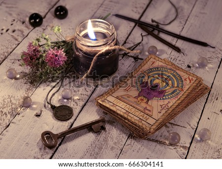 Black candle and old tarot cards on wooden planks. Halloween and fortune telling concept. Mystic background with occult and magic objects on witch table.  #666304141