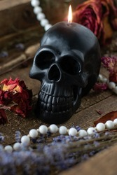 Black candle scull on witch table. Occult, esoteric, divination and wicca concept. Halloween concept