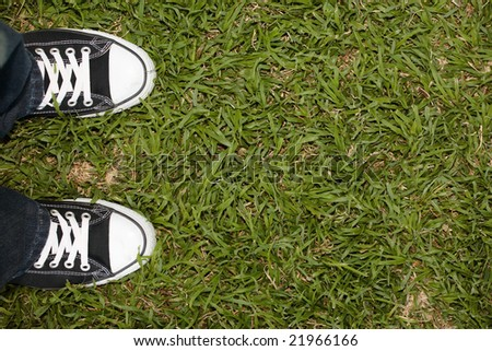Black canvas sneakers on grass, copy space on the right
