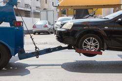 Black car crash damage delivers to garage by blue truck.