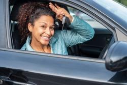 Black car driver woman smiling showing new car keys and car
