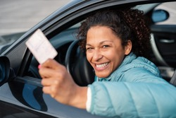 Black car driver woman smiling showing new driver's license