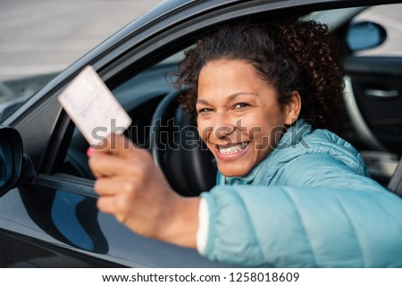 Black car driver woman smiling showing new driver's license #1258018609