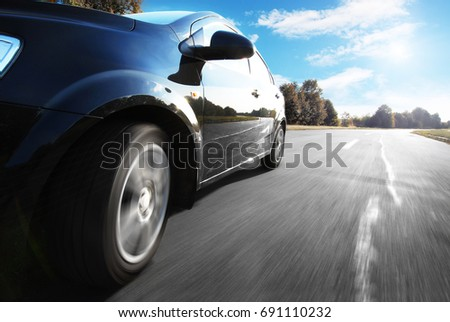 Black car driving fast on a road against blue sky in the countryside