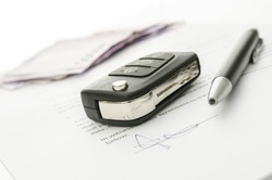 Black car key and money on a signed contract of car sale.  Focus on a key.