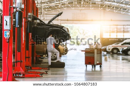 black car repair station with soft-focus and over light in the background #1064807183