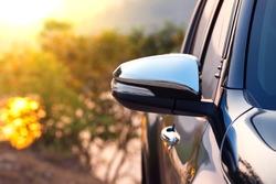 Black car side mirror with sun light effect.