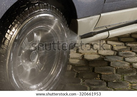 Black car tire getting detailed wash from high pressure water cleaner. #320661953