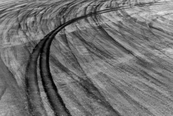 Black car tire skid mark on asphalt road track texture and background, Automobile and automotive car drift skid mark on race track.