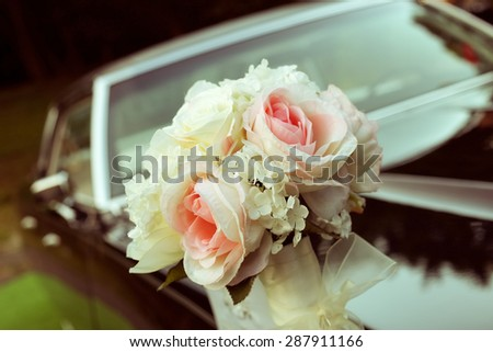 Black car with a delicate bouquet of roses. Wedding car decoration. A special day, wedding, holiday. A bouquet of artificial flowers. Floristry, decoration of the wedding.
