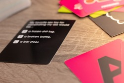 Black card representing a card board game. Answers blurred but barely visible. Multiple cards on the table, pink A in the corner.