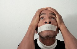 black Caribbean men feeling the pain after being discriminated with tape over his mouth on white background stock photo