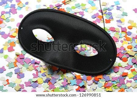 black carnival mask on colorful confetti