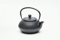 Black cast iron teapot on a white background. Asian culture.