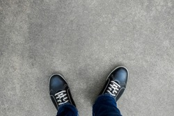 Black casual shoes standing and resting on asphalt concrete floor. Making decision what to do next