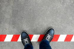 Black casual shoes standing on red and white line. Crossing the limit. Disobey and act against the rule.