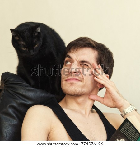 black cat cuddles up to the man reading a book