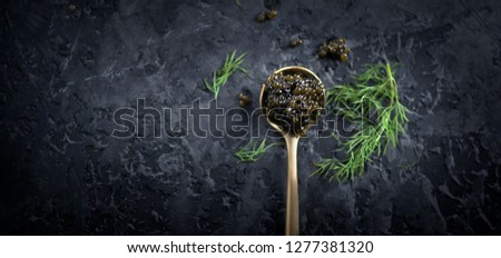 Black Caviar in a spoon on dark background. High quality real natural sturgeon black caviar close-up. Delicatessen. Texture of expensive luxury caviar. Food Backdrop. Top view, flatlay