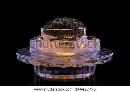 Black caviar in glows ice isolated on black