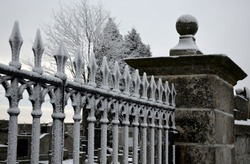 black cemetery gate made of heavy cast metal. the lattice is in the shape of spears. a column of granite stone topped by a sphere. circles and decorative handle.