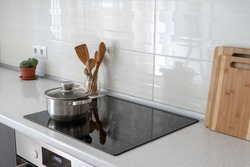 Black ceramic induction stove with pot, pan on clean surface. Modern apartment with contemporary interior, built in kitchen appliance, white tile on wall and decor plant in flowerpot
