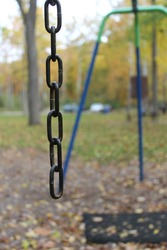 black chain hanging down from a swing set with a blurred background