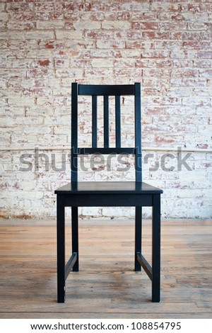 Black chair in front of a brick wall.